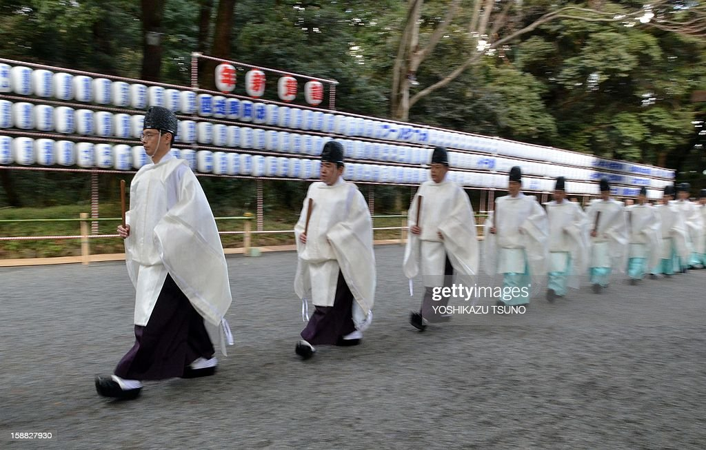 Shinto priests walk in a line on the approach to Meiji Shrine for the annual end-of-the-year purification ceremony to prepare for New Year's Day in Tokyo on December 31, 2012. Millions of Japanese people will visit shrines and temples across the country to celebrate New Year's Day, one of the most important holiday periods of the year here. AFP PHOTO / Yoshikazu TSUNO