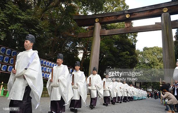 Shinto priests walk in a line through a large wooden gate known as a 'torii' for the annual endoftheyear purification ceremony to prepare for New...