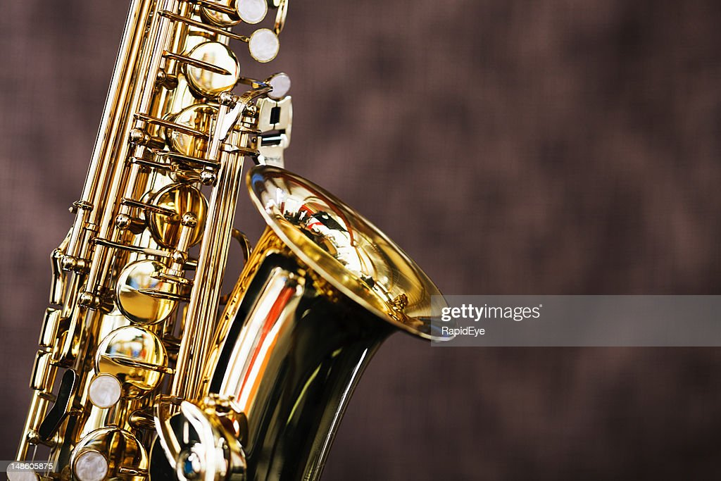 Shiny bright saxophone in close up against brown background : Stock Photo