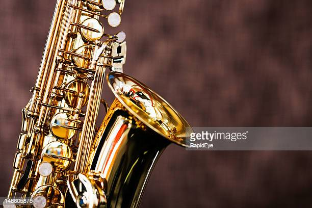 Shiny bright saxophone in close up against brown background