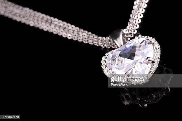 Shiny, heart-shaped diamond pendant on silver colored chain