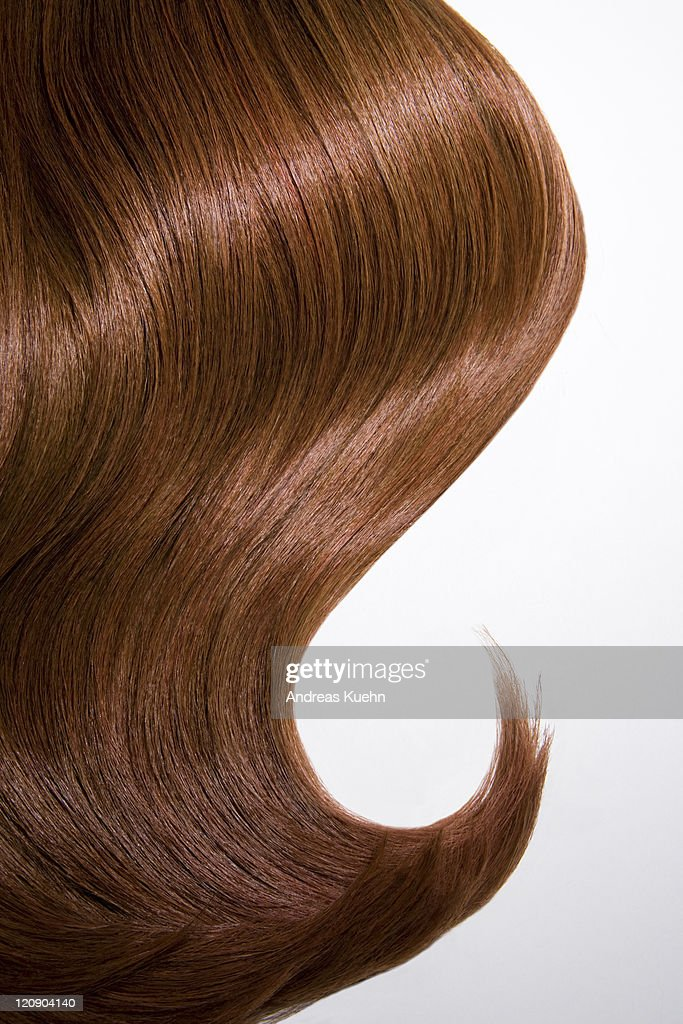 Shiny wavy red hair on white background, cropped.