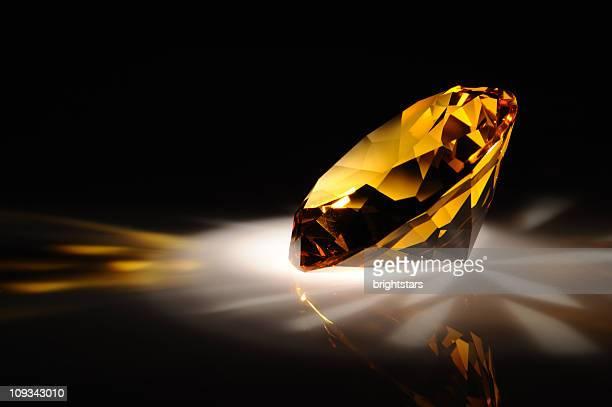 Shiny yellow diamond in dark