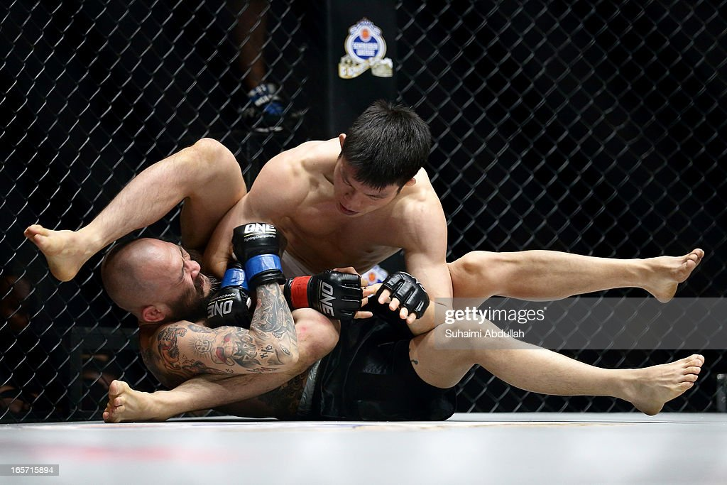 Shinya Aoki of Japan (back) fights Kotetsu Boku of Japan for the Lightweight World Championship bout during the One Fighting Championship at Singapore Indoor Stadium on April 5, 2013 in Singapore.