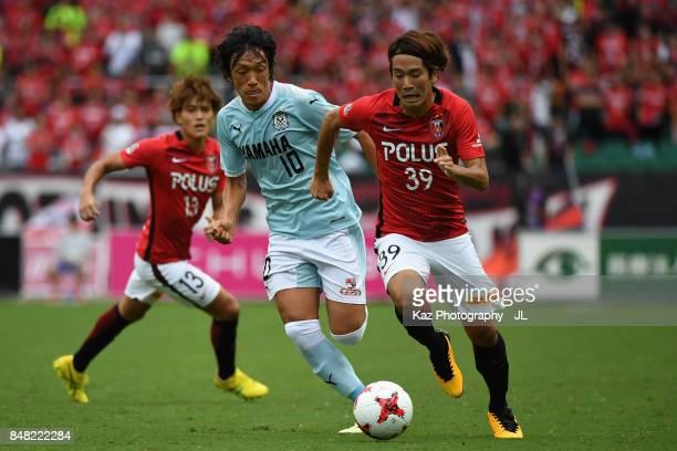 Shinya Yajima of Urawa Red Diamonds and Shunsuke Nakamura of Jubilo Iwata compete for the ball during the JLeague J1 match between Jubilo Iwata and...