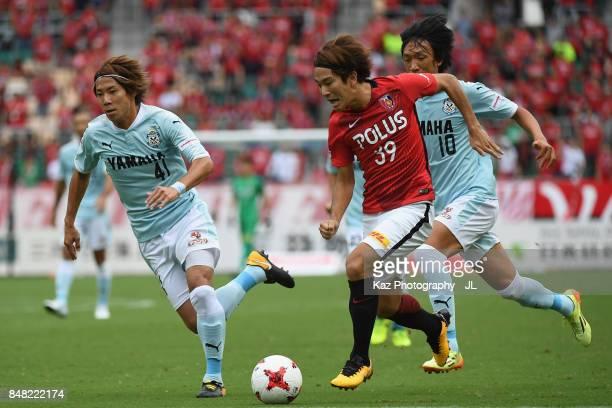 Shinya Yajima of Urawa Red Diamonds competes for the ball against Shohei Takahashi and Shunsuke Nakamura of Jubilo Iwata during the JLeague J1 match...