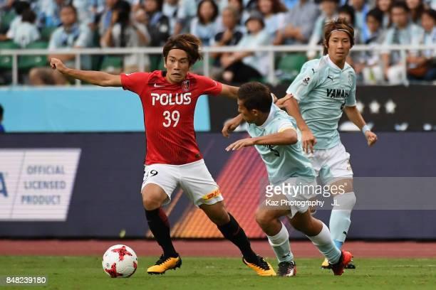 Shinya Yajima of Urawa Red Diamonds takes on Kentaro Oi of Jubilo Iwata during the JLeague J1 match between Jubilo Iwata and Urawa Red Diamonds at...