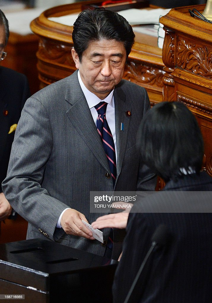 Shinzo Abe (facing) casts his ballot to elect new Japanese prime minister at the lower house of parliament in Tokyo on December 26, 2012. The powerful lower house named the 58-year-old Abe as the country's new leader following a resounding national election victory for Abe's Liberal Democratic Party earlier this month over the booted Democratic Party of Japan (DPJ). AFP PHOTO/Toru YAMANAKA