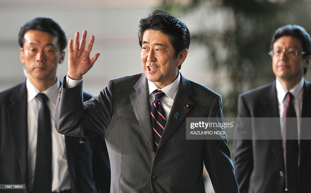 Shinzo Abe (C), elected by the parliament as Japan's prime minister, arrives at the prime minster's official residence in Tokyo on December 26, 2012. The powerful lower house named the 58-year-old as the country's new leader following a resounding national election victory for Abe's Liberal Democratic Party earlier this month over the booted Democratic Party of Japan NOGI