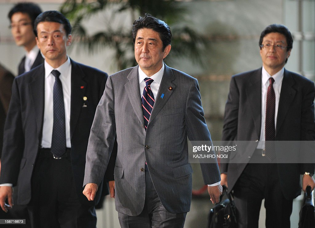 Shinzo Abe (C), elected by the parliament as Japan's prime minister, arrives at the prime minister's official residence in Tokyo on December 26, 2012. The powerful lower house named the 58-year-old as the country's new leader following a resounding national election victory for Abe's Liberal Democratic Party earlier this month over the booted Democratic Party of Japan NOGI