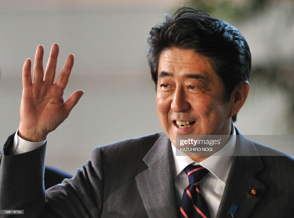 Shinzo Abe (C), electedd by the parliament as Japan's prime minister, waves to the media upon his arrival at the prime minster's official residence in Tokyo on December 26, 2012. The powerful lower house named the 58-year-old as the country's new leader following a resounding national election victory for Abe's Liberal Democratic Party earlier this month over the booted Democratic Party of Japan NOGI
