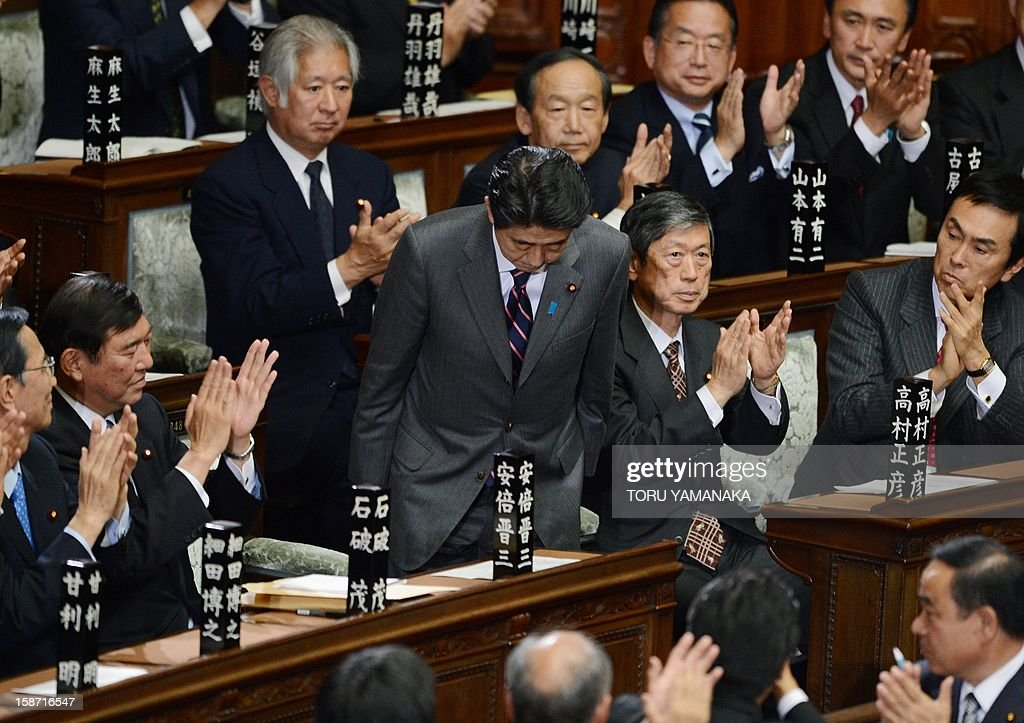 Shinzo Abe (C) is applauded by parliament members after he was elected as Japan's prime minister by the lower house of parliament in Tokyo on December 26, 2012. The powerful lower house named the 58-year-old as the country's new leader following a resounding national election victory for Abe's Liberal Democratic Party earlier this month over the booted Democratic Party of Japan (DPJ) AFP PHOTO/Toru YAMANAKA