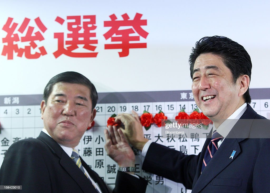 <a gi-track='captionPersonalityLinkClicked' href=/galleries/search?phrase=Shinzo+Abe&family=editorial&specificpeople=559017 ng-click='$event.stopPropagation()'>Shinzo Abe</a>, Japan's former prime minister and president of the Liberal Democratic Party (LDP), right, poses with <a gi-track='captionPersonalityLinkClicked' href=/galleries/search?phrase=Shigeru+Ishiba&family=editorial&specificpeople=2921096 ng-click='$event.stopPropagation()'>Shigeru Ishiba</a>, secretary general of the LDP, as they place a red paper rose on a LDP candidate's name to indicate an election victory at the party's headquarters in Tokyo, Japan, on Sunday, Dec. 16, 2012. Japan's LDP won parliamentary elections to reclaim power three years after surrendering half a century of control, ensuring the country will get its seventh leader in six years, exit polls showed. Photographer: Tomohiro Ohsumi/Bloomberg via Getty Images