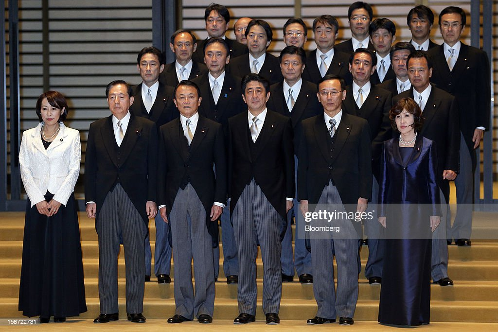 Shinzo Abe, Japan's new prime minister, third from right in the front row, poses for a group photograph with Masako Mori, newly named minister for consumer affairs and gender equality, from left in the front row, Akihiro Ohta, newly appointed land, infrastructure, and transport minister, Taro Aso, newly appointed deputy prime minister and minister for finance and financial services, Sadakazu Tanigaki, newly appointed justice minister, Tomomi Inada, newly appointed administrative reform minister, and other new cabinet members after the attestation ceremony at the Imperial Palace in Tokyo, Japan, on Wednesday, Dec. 26, 2012. Japan's lower house confirmed Abe as the nation's seventh prime minister in six years, returning him to the office he left in 2007 after his party regained power in a landslide election victory last week. Photographer: Kiyoshi Ota/Bloomberg via Getty Images