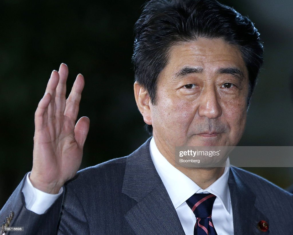 Shinzo Abe, Japan's newly elected prime minister, waves to the media upon his arrival at the prime minister's official residence in Tokyo, Japan, on Wednesday, Dec. 26, 2012. Japan's lower house confirmed Abe as the nation's seventh prime minister in six years, returning him to the office he left in 2007 after his party regained power in a landslide election victory last week. Photographer: Kiyoshi Ota/Bloomberg via Getty Images