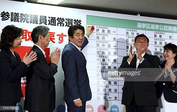 Shinzo Abe Japan's prime minister and president of the Liberal Democratic Party center places a red paper rose on an LDP candidate's name to indicate...