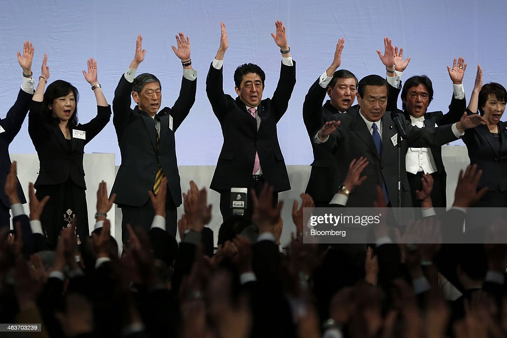 <a gi-track='captionPersonalityLinkClicked' href=/galleries/search?phrase=Shinzo+Abe&family=editorial&specificpeople=559017 ng-click='$event.stopPropagation()'>Shinzo Abe</a>, Japan's prime minister and president of the Liberal Democratic Party (LDP), center, cheers with <a gi-track='captionPersonalityLinkClicked' href=/galleries/search?phrase=Seiko+Noda&family=editorial&specificpeople=2255707 ng-click='$event.stopPropagation()'>Seiko Noda</a>, chairperson of the General Council, left, <a gi-track='captionPersonalityLinkClicked' href=/galleries/search?phrase=Masahiko+Komura&family=editorial&specificpeople=2591868 ng-click='$event.stopPropagation()'>Masahiko Komura</a>, vice president, second left, <a gi-track='captionPersonalityLinkClicked' href=/galleries/search?phrase=Shigeru+Ishiba&family=editorial&specificpeople=2921096 ng-click='$event.stopPropagation()'>Shigeru Ishiba</a>, secretary general, fourth from right, Sanae Takaichi, chairperson of the Policy Research Council, right, and other party members during the Liberal Democratic Party's (LDP) annual convention in Tokyo, Japan, on Sunday, Jan. 19, 2014. Abe will raise the consumption tax in April to 8 percent from 5 percent to help contain the nations swelling public debt. Photographer: Kiyoshi Ota/Bloomberg via Getty Images