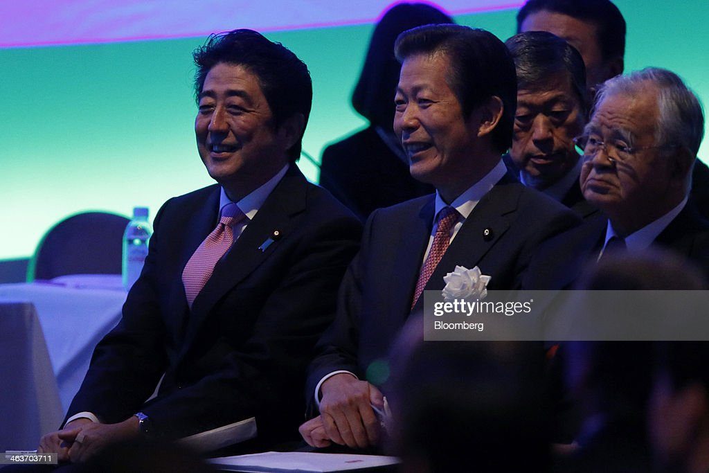 Shinzo Abe, Japan's prime minister and president of the Liberal Democratic Party (LDP), left, reacts as he sits next to Natsuo Yamaguchi, chief representative of the New Komeito Party, while <a gi-track='captionPersonalityLinkClicked' href=/galleries/search?phrase=Hiromasa+Yonekura&family=editorial&specificpeople=2816307 ng-click='$event.stopPropagation()'>Hiromasa Yonekura</a>, chairman of Sumitomo Chemical Co. and chairman of the business lobby Keidanren, right, looks on during the Liberal Democratic Party's (LDP) annual convention in Tokyo, Japan, on Sunday, Jan. 19, 2014. Abe will raise the consumption tax in April to 8 percent from 5 percent to help contain the nations swelling public debt. Photographer: Kiyoshi Ota/Bloomberg via Getty Images