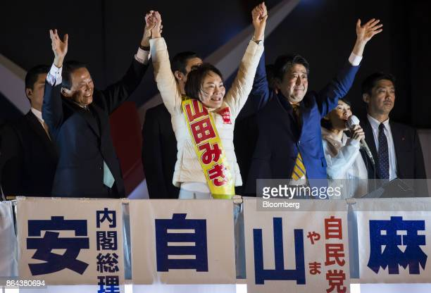 Shinzo Abe Japan's prime minister and president of the Liberal Democratic Party right raises his arms as he cheers with Taro Aso Japan's deputy prime...