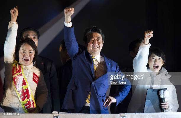 Shinzo Abe Japan's prime minister and president of the Liberal Democratic Party center raises his arm with a party candidate during an election...