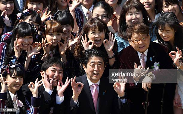 Shinzo Abe Japan's prime minister center in the front row poses for photographers with guest attendees including members from a girl idol group 'HKT...