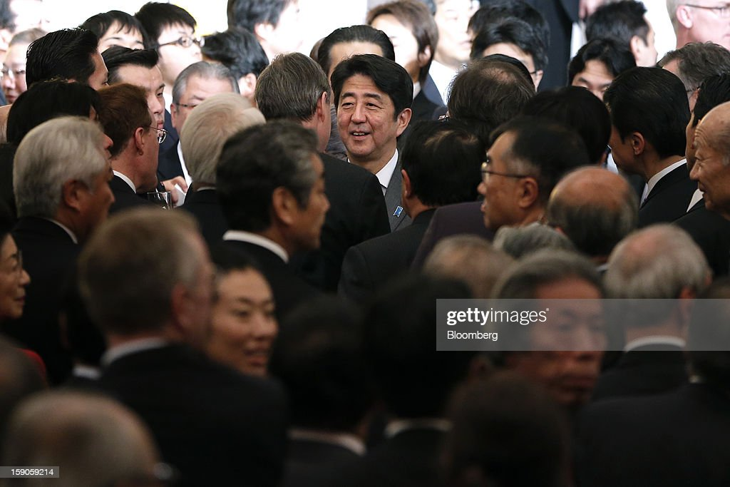 Shinzo Abe, Japan's prime minister, center, speaks with guests during a New Year's party for business leaders in Tokyo, Japan, on Monday, Jan. 7, 2013. The Japanese government will announce around 12 trillion yen ($136 billion) in fiscal stimulus measures to boost the nation's shrinking economy, Japanese media reported today. Photographer: Kiyoshi Ota/Bloomberg via Getty Images