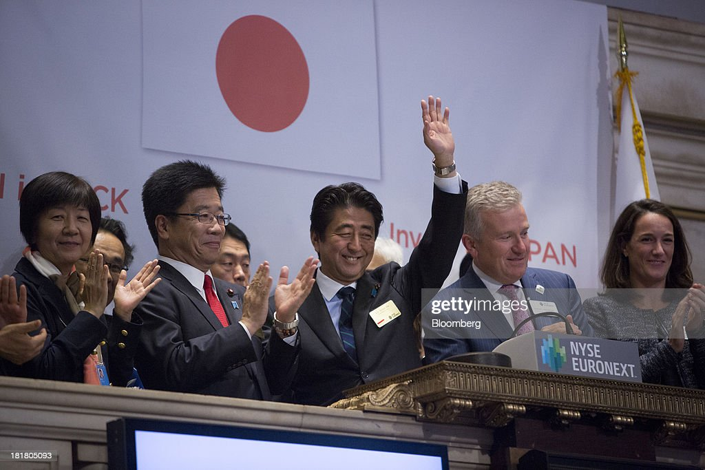 <a gi-track='captionPersonalityLinkClicked' href=/galleries/search?phrase=Shinzo+Abe&family=editorial&specificpeople=559017 ng-click='$event.stopPropagation()'>Shinzo Abe</a>, Japan's prime minister, center, waves to the trading floor after ringing the closing bell at the New York Stock Exchange (NYSE) in New York, U.S., on Wednesday, Sept. 25, 2013. Abe's pledge to end 15 years of deflation and the Bank of Japan's monetary policy easing, along with Tokyo's winning bid to host the 2020 Olympic Games have helped boost consumer sentiment. Photographer: Scott Eells/Bloomberg via Getty Images