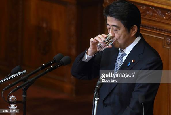 Shinzo Abe Japan's prime minister drinks a glass of water as he delivers a policy speech during an extraordinary session at the lower houses of the...