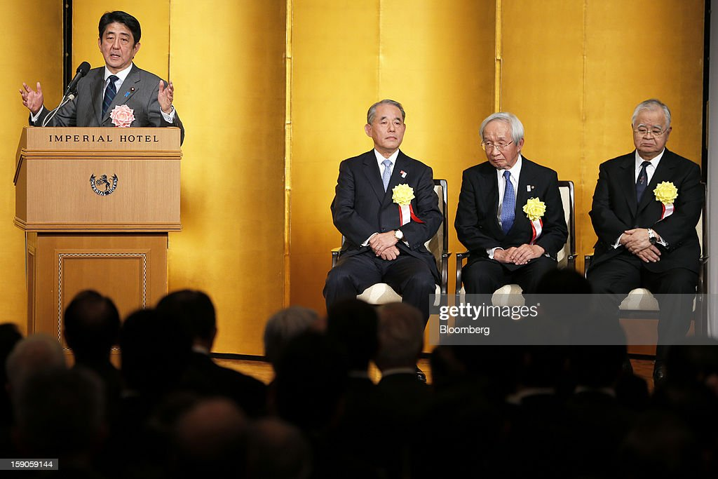 Shinzo Abe, Japan's prime minister, from left, speaks as Yasuchika Hasegawa, president of Takeda Pharmaceutical Co. and chairman of the business lobby Keizai Doyukai, Tadashi Okamura, advisor to Toshiba Corp. and chairman of the Japan Chamber of Commerce and Industry (JCCI), and Hiromasa Yonekura, chairman of Sumitomo Chemical Co. and chairman of the business lobby Keidanren, listen during a New Year's party for business leaders in Tokyo, Japan, on Monday, Jan. 7, 2013. The Japanese government will announce around 12 trillion yen ($136 billion) in fiscal stimulus measures to boost the nation's shrinking economy, Japanese media reported today. Photographer: Kiyoshi Ota/Bloomberg via Getty Images