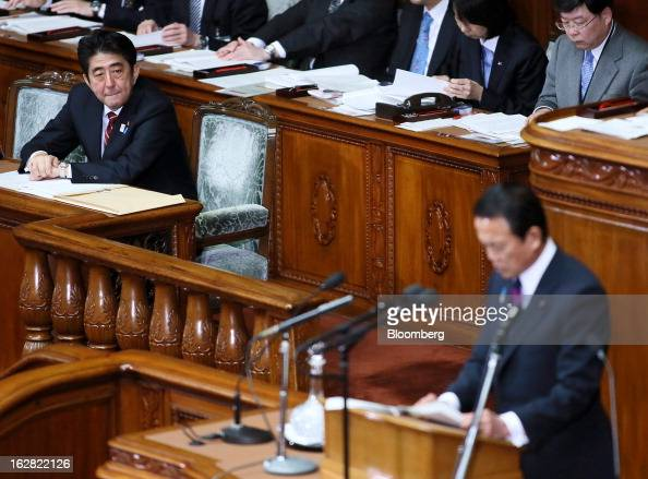 Shinzo Abe Japan's prime minister left looks on as Taro Aso Japan's deputy prime minister and finance minister delivers his policy speech at the...