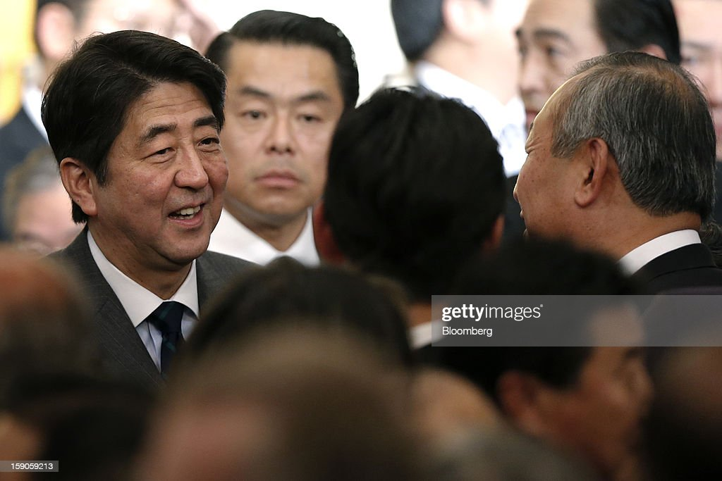 Shinzo Abe, Japan's prime minister, left, speaks with guests during a New Year's party for business leaders in Tokyo, Japan, on Monday, Jan. 7, 2013. The Japanese government will announce around 12 trillion yen ($136 billion) in fiscal stimulus measures to boost the nation's shrinking economy, Japanese media reported today. Photographer: Kiyoshi Ota/Bloomberg via Getty Images