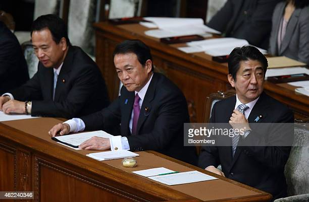 Shinzo Abe Japan's prime minister right adjusts his tie as Taro Aso deputy prime minister and finance minister center and Akira Amari economic...
