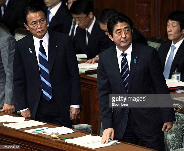Shinzo Abe Japan's prime minister right and Taro Aso Japan's deputy prime minister and finance minister attend the opening session of the Diet at the...