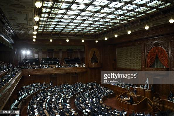Shinzo Abe Japan's prime minister right delivers a policy speech during an extraordinary session at the lower houses of the parliament in Tokyo Japan...