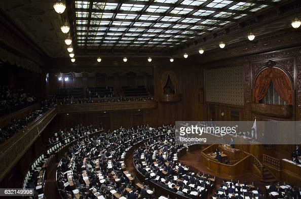 Shinzo Abe Japan's prime minister right delivers his policy speech during a plenary session at the lower house of the parliament in Tokyo Japan on...