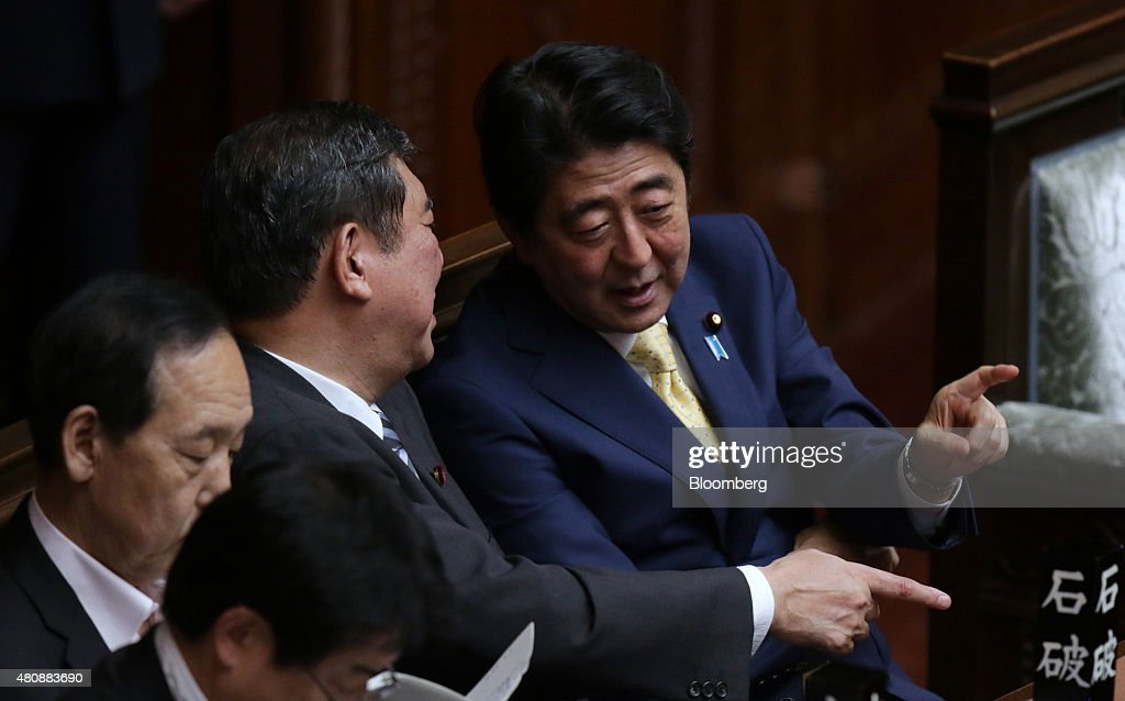 <a gi-track='captionPersonalityLinkClicked' href=/galleries/search?phrase=Shinzo+Abe&family=editorial&specificpeople=559017 ng-click='$event.stopPropagation()'>Shinzo Abe</a>, Japan's prime minister, right, speaks with <a gi-track='captionPersonalityLinkClicked' href=/galleries/search?phrase=Shigeru+Ishiba&family=editorial&specificpeople=2921096 ng-click='$event.stopPropagation()'>Shigeru Ishiba</a>, minister in charge of regional revitalization, center, during a plenary session at the lower house of the parliament in Tokyo, Japan, on Wednesday, July 15, 2015. Japanese Prime Minister <a gi-track='captionPersonalityLinkClicked' href=/galleries/search?phrase=Shinzo+Abe&family=editorial&specificpeople=559017 ng-click='$event.stopPropagation()'>Shinzo Abe</a>'s security bills passed parliament's lower house Thursday after a night of noisy protests, as his push to expand the role of the military risks further eroding his public support. Photographer: Tomohiro Ohsumi/Bloomberg via Getty Images