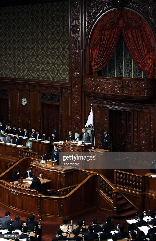Shinzo Abe, Japan's prime minister, standing at podium, delivers his policy speech during the opening session of the Diet at the lower house of parliament in Tokyo, Japan, on Monday, Jan. 28, 2013. Abe's government predicts that tax revenue will exceed cash raised from bond sales for the first time in four years as the nation's economy emerges from last year's recession. Photographer: Haruyoshi Yamaguchi/Bloomberg via Getty Images