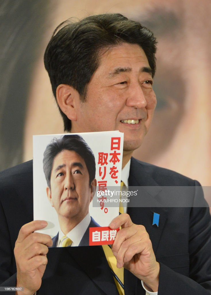 Shinzo Abe, president of Japan's main opposition Liberal Democratic Party (LDP), holds up a booklet of the party's pledges as he speaks during a news conference to announce the pledges for the December 16 lower house election, at the LDP headquarters in Tokyo on November 21, 2012. Opinion polls published on November 19 showed Japan's main opposition party out in front days after Prime Minister Yoshihiko Noda set the country on the path to a general election. AFP PHOTO / KAZUHIRO NOGI