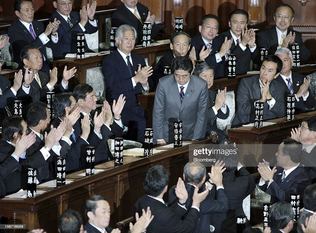 <a gi-track='captionPersonalityLinkClicked' href=/galleries/search?phrase=Shinzo+Abe&family=editorial&specificpeople=559017 ng-click='$event.stopPropagation()'>Shinzo Abe</a>, president of the Liberal Democratic Party (LDP), center, bows as he is applauded after being elected Japan's prime minister at the lower house of parliament in Tokyo, Japan, on Wednesday, Dec. 26, 2012. Japan's lower house confirmed Abe as the nation's seventh prime minister in six years, returning him to the office he left in 2007 after his party regained power in a landslide election victory last week. Photographer: Haruyoshi Yamaguchi/Bloomberg via Getty Images