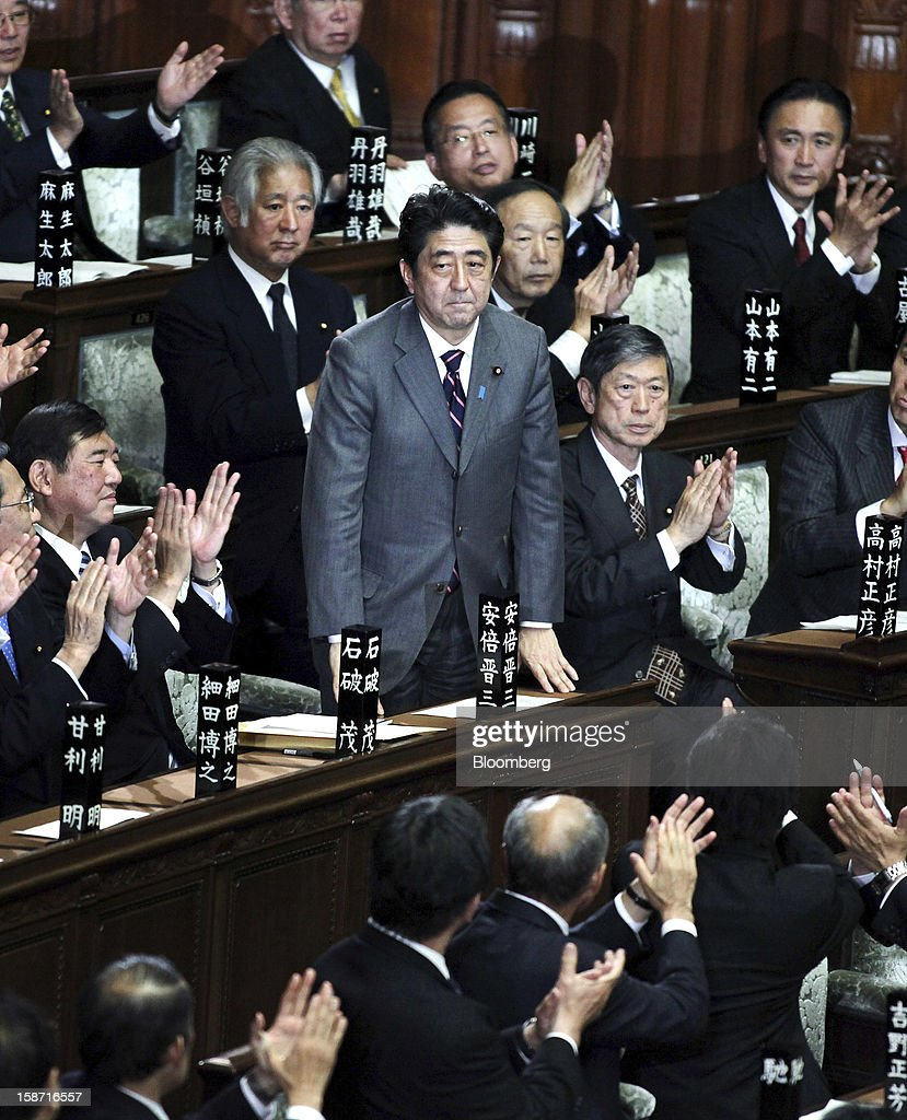 <a gi-track='captionPersonalityLinkClicked' href=/galleries/search?phrase=Shinzo+Abe&family=editorial&specificpeople=559017 ng-click='$event.stopPropagation()'>Shinzo Abe</a>, president of the Liberal Democratic Party (LDP), center, is applauded after being elected Japan's prime minister at the lower house of parliament in Tokyo, Japan, on Wednesday, Dec. 26, 2012. Japan's lower house confirmed Abe as the nation's seventh prime minister in six years, returning him to the office he left in 2007 after his party regained power in a landslide election victory last week. Photographer: Haruyoshi Yamaguchi/Bloomberg via Getty Images
