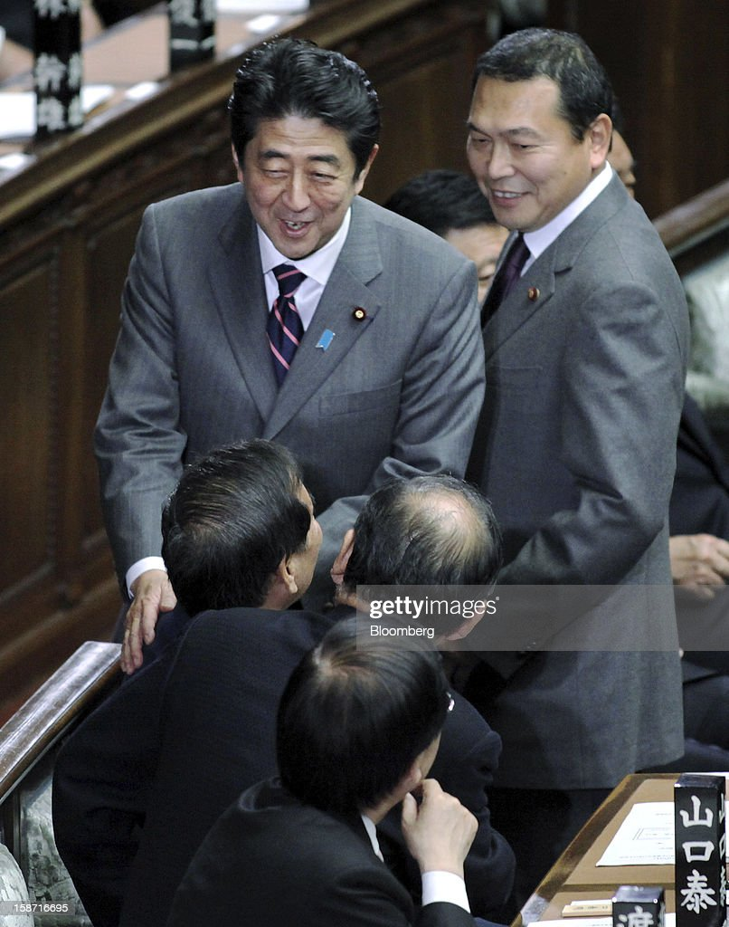 Shinzo Abe, president of the Liberal Democratic Party (LDP), center, speaks to a LDP lawmaker after casting his ballot before being elected Japan's prime minister at the lower house of parliament in Tokyo, Japan, on Wednesday, Dec. 26, 2012. Japan's lower house confirmed Abe as the nation's seventh prime minister in six years, returning him to the office he left in 2007 after his party regained power in a landslide election victory last week. Photographer: Haruyoshi Yamaguchi/Bloomberg via Getty Images
