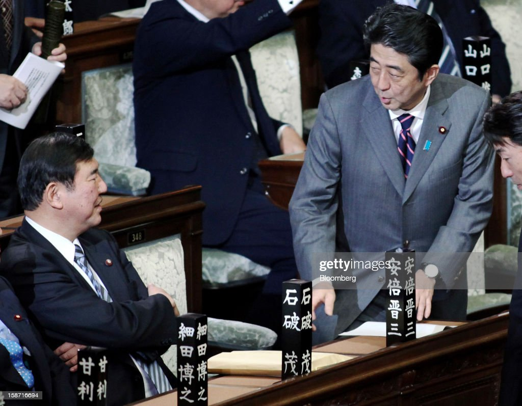 Shinzo Abe, president of the Liberal Democratic Party (LDP), right, speaks to Shigeru Ishiba, secretary general of the party, before being elected Japan's prime minister at the lower house of parliament in Tokyo, Japan, on Wednesday, Dec. 26, 2012. Japan's lower house confirmed Abe as the nation's seventh prime minister in six years, returning him to the office he left in 2007 after his party regained power in a landslide election victory last week. Photographer: Haruyoshi Yamaguchi/Bloomberg via Getty Images