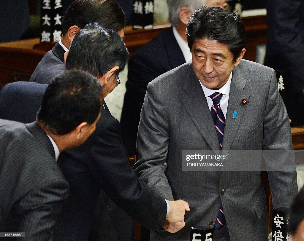 Shinzo Abe (R) shakes hands with parliament members after he was elected as Japan's prime minister by the lower house of parliament in Tokyo on December 26, 2012. The powerful lower house named the 58-year-old as the country's new leader following a resounding national election victory for Abe's Liberal Democratic Party earlier this month over the booted Democratic Party of Japan (DPJ). AFP PHOTO/Toru YAMANAKA