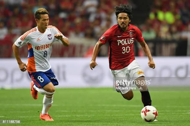 Shinzo Koroki of Urawa Red Diamonds and Kei Koizumi of Albirex Niigata compete for the ball during the JLeague J1 match between Urawa Red Diamonds...