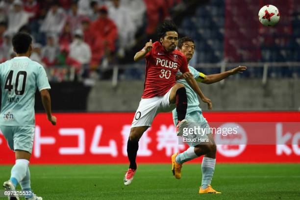 Shinzo Koroki of Urawa Red Diamonds and Kentaro Oi of Jubilo Iwata compete for the ball during the JLeague J1 match between Urawa Red Diamonds and...