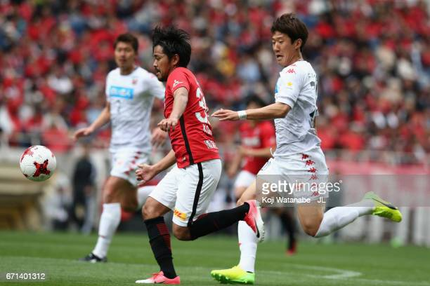 Shinzo Koroki of Urawa Red Diamonds and Kim Min Tae of Consadole Sapporo compete for the ball during the JLeague J1 match between Urawa Red Diamonds...