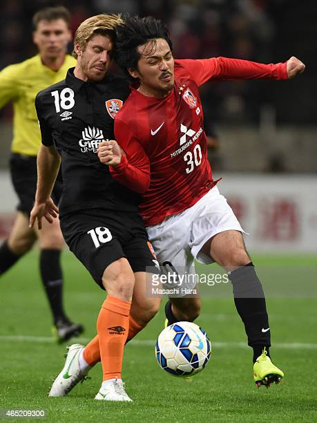 Shinzo Koroki of Urawa Red Diamonds and Luke Brattan of Brisbane Roar compete for the ball during the AFC Champions League Group G match between...