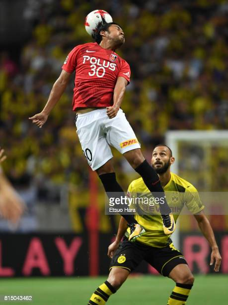 Shinzo Koroki of Urawa Red Diamonds and Oemer Toprak of Burussia Dortmund compete for the ball during the preseason friendly match between Urawa Red...