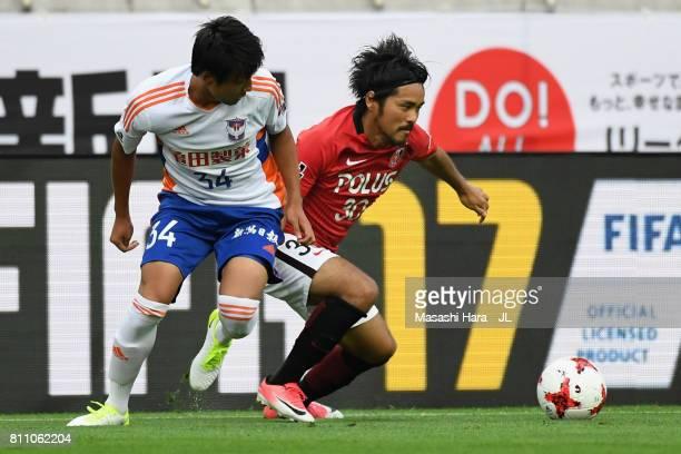 Shinzo Koroki of Urawa Red Diamonds and Teruki Hara of Albirex Niigata compete for the ball during the JLeague J1 match between Urawa Red Diamonds...