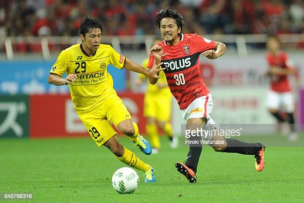 Shinzo Koroki of Urawa Red Diamonds and Yuta Nakayama of Kashiwa Reysol compete for the ball during the JLeague match between Urawa Red Diamonds and...
